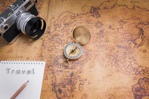 Vintage Compass and camera on map for travel planning photo