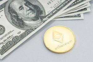 Ethereum coin and a pile of US dollar banknotes photo