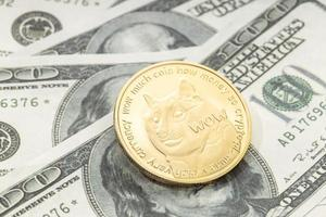 Dogecoin coin on dollar banknotes. Cryptocurrency on US dollar bills photo