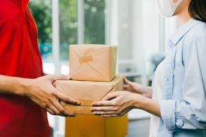close up delivery man in red uniform deliver service parcel box photo