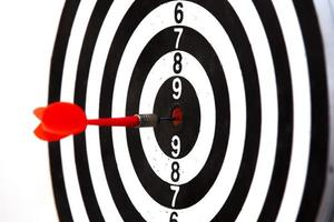 Dartboard with dart arrow hitting the center. Marketing concept. photo