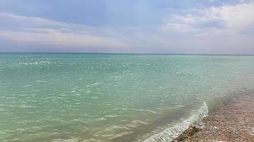 Seascape. Azure color of water, waves foaming on the shore. photo