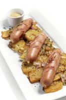 Salchichas de cerdo y queso orgánico alemán con patatas fritas y mostaza sobre fondo blanco. foto