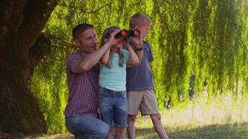 Father and children looking through binoculars video