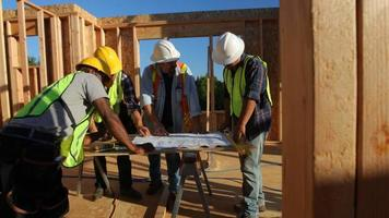 Group of construction workers look at plans video