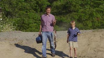 Father and son walking with fish video