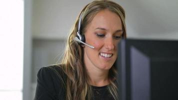 femme d'affaires parlant avec un casque au bureau video