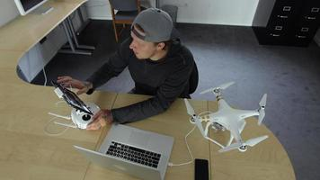 El hombre en la oficina conecta el dron a la computadora video
