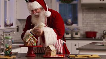 le père noël dans la cuisine décorant la maison en pain d'épice video