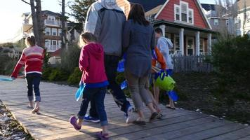 Family walking up wooden pathway to beach video