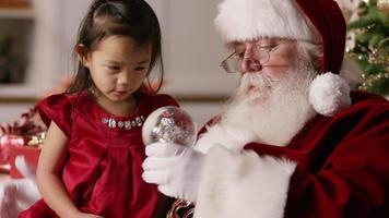 le père noël montre une boule à neige à une petite fille video