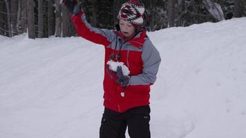 Boy throwing snowballs in slow motion video