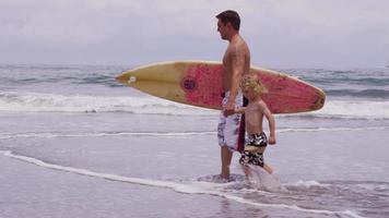 padre e figlio che camminano con la tavola da surf. video
