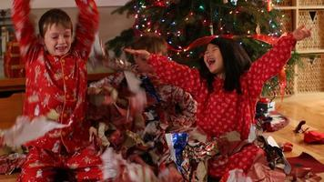 Three kids throwing Christmas wrapping paper video