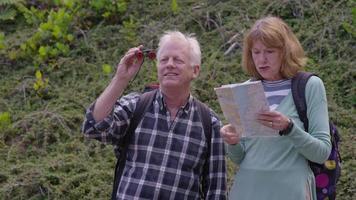 Las parejas ancianas en caminata mirando a través de binoculares video