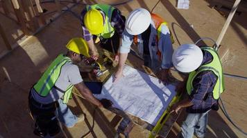 Overhead shot of construction workers looking at plans video