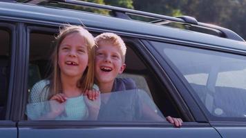 deux enfants regardant par la fenêtre de la voiture video