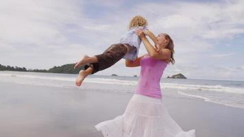 mamma svängande son på stranden. video