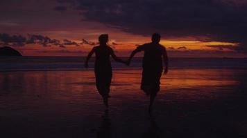 Couple run out to ocean at sunset, Costa Rica. video