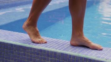 närbild av fötter som går vid poolen och doppar tå i vatten. video