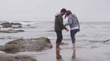 paar wandelen op het strand samen. video