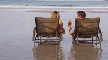 coppia con cocktail tropicali in spiaggia. video