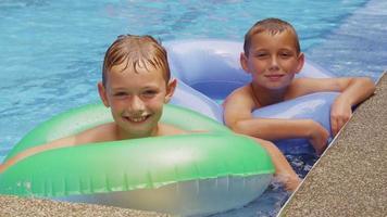 dos chicos en piscina con llantas. video