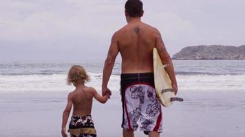 padre e figlio con la tavola da surf che escono verso l'oceano. video