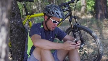 Man with mountain bike sits down taking break and checking cell phone video