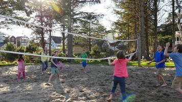 Family playing at sand volleyball court video