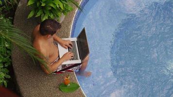 uomo seduto sul bordo della vasca idromassaggio utilizzando il computer portatile. video