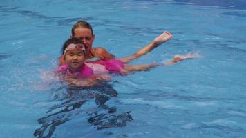 mamma lär dotter att simma i poolen. video