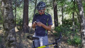 Mountain biker takes a break to check cell phone video