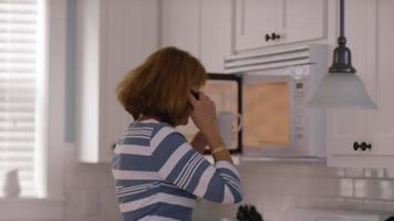 donna anziana in cucina al cellulare video