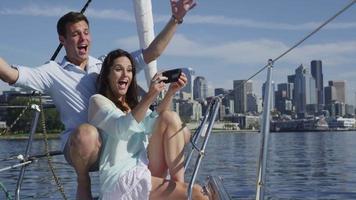 ungt par på segelbåt tillsammans med mobiltelefon. video