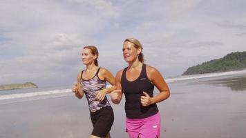 dos mujeres corriendo juntas en la playa. rodado en rojo épico video