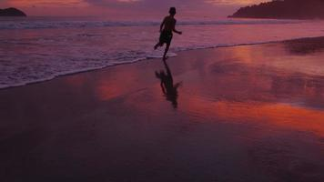 pojke springer på stranden vid solnedgången, costa rica. video