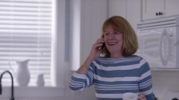 donna anziana in cucina con caffè sul cellulare video