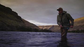 homem pescando com mosca no lindo rio ao nascer do sol video