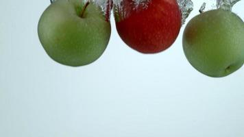 maçãs caindo na água em câmera lenta video
