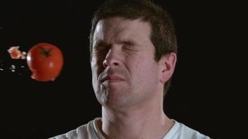 Toma de cámara lenta de tomate golpeando a hombre en la cara video