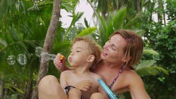 mamma och son leker med bubblor. video