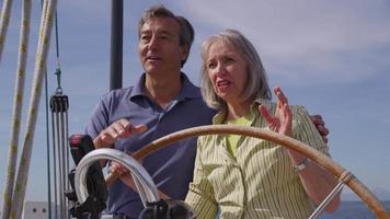 seniorpar bakom ratten på segelbåt tillsammans. video