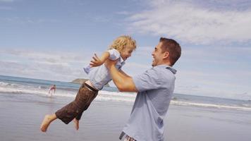 far svängande son på stranden. video