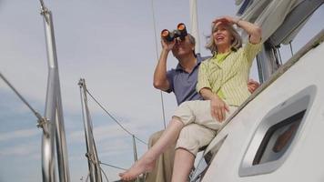 seniorpar som tittar genom kikare på segelbåt tillsammans video