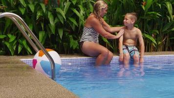 mamma lägger solskyddsmedel på solen vid poolen. video