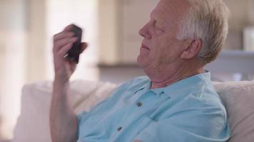uomo anziano in soggiorno che parla al cellulare video