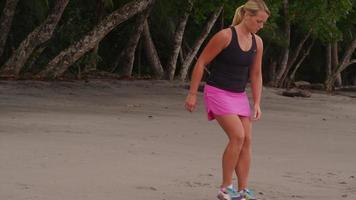 dos mujeres en la playa estirándose y preparándose para correr. video