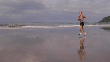 mujer corriendo en la playa, cámara lenta. video