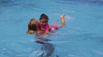 mamma och dotter leker i poolen. video